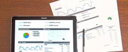 Foto de um tablet com a imagem de gráficos e estatísticas. Atrás deste, há duas folhas também de gráficos posicionadas na lateral direita e uma caneta.