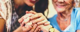 Fotografia de uma senhora idosa e uma moça sorridentes. A moça segura as mãos da senhora entre as suas.