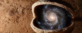 Foto montagem. Em frente a uma parede de madeira, uma pedra marrom, redonda, com uma abertura central, revela em seu interior a imagem do universo com a Via Láctea e várias constelações.