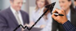 Foto montagem na qual a mão de uma pessoa segurando uma caneta desenha uma seta preta ascendente, como em um gráfico. Ao fundo, desfocados, há duas mulheres e um homem e bem vestidos olhando uma prancheta.
