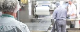 Na foto, dois homens e uma mulher usam avental, touca e máscara brancos. Trabalham junto a estruturas metálicas que remetem à uma linha de produção industrial.