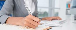 Foto de uma mulher, vestindo camisa e blazer, sentada à mesa de escritório. Com uma mão faz anotações em uma agenda e, com a outra, digita ao computador. Destaque para sua mão. Seu rosto não está aparente.