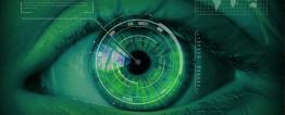 Foto em tons de verde de um olho. Sobre a íris há um círculo digital e do centro da pupila saem informações em forma de texto e mapa.