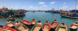 Foto de diversos pequenos barcos em um porto.
