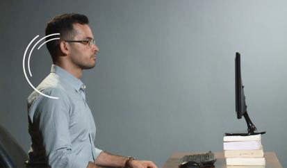 Foto de um homem sentado à frente do computador, com a coluna ereta. Sinais gráficos indicam a inclinação da cabeça para que a tela do computador fique na altura dos olhos.